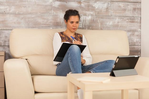 Femme prenant des notes lors d'un appel vidéo avec des collègues tout en travaillant à domicile.
