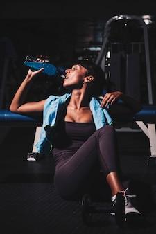 Femme prenant une pause en salle de sport