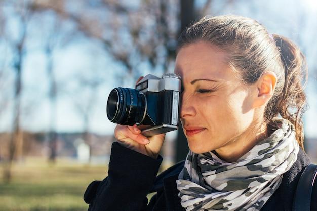 Femme prenant une photo avec un appareil photo analogique