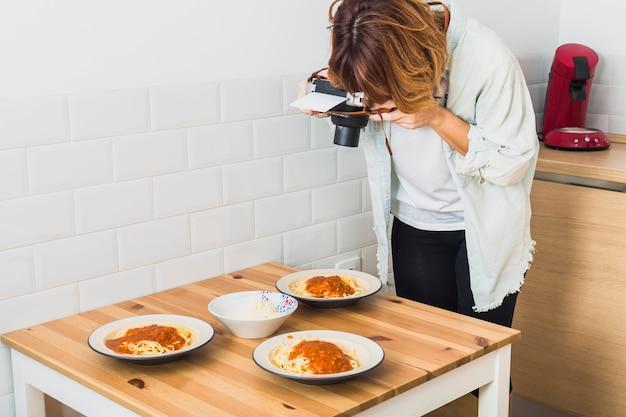 Femme prenant la photo des assiettes de nourriture