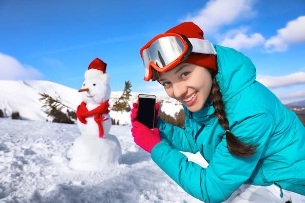 Femme prenant une photo de bonhomme de neige à la station de ski.
