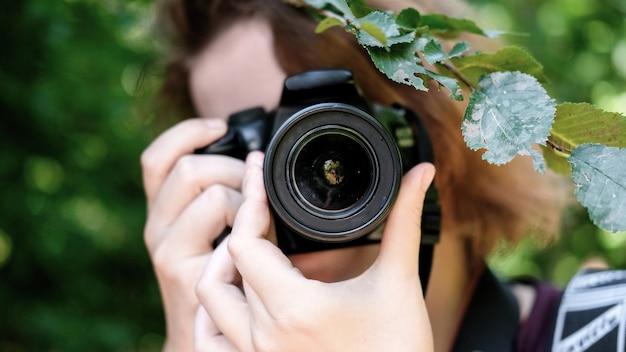 Femme prenant une photo d'une caméra principale à l'aide d'une caméra professionnelle. verdure autour