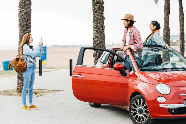 Femme prenant une photo d'un couple en voiture