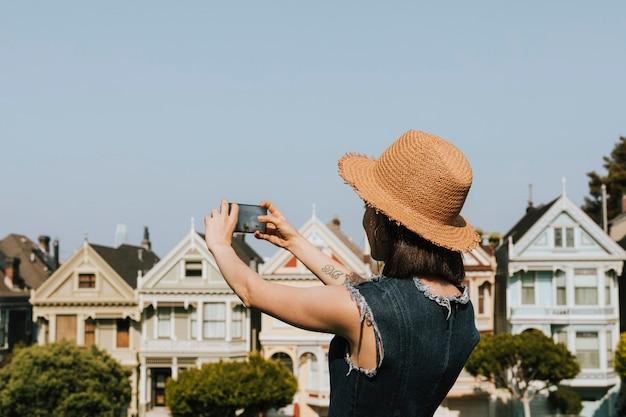 Femme prenant une photo des dames peintes de san francisco, états-unis
