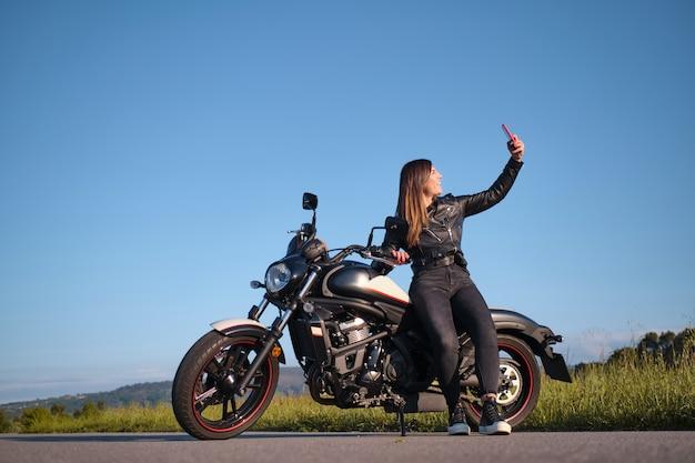 Femme prenant une photo avec une moto