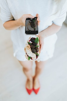 Femme prenant une photo d'un pain grillé avec de la confiture de mûres et du fromage à la crème végétalien