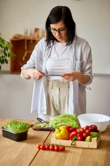 Femme prenant une photo de salade saine avec smartphone pour son blog sur la cuisine à la maison