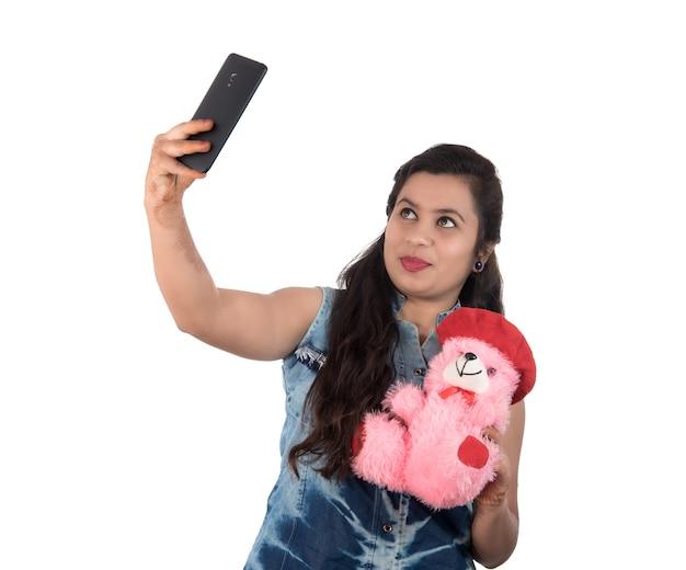 Femme prenant une photo ou selfie avec un téléphone mobile et tenant un ours en peluche