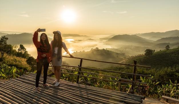 Femme prenant une photo avec un smartphone au sommet de la montagne