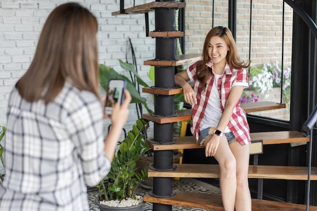 Femme prenant une photo de son amie avec un smartphone au café