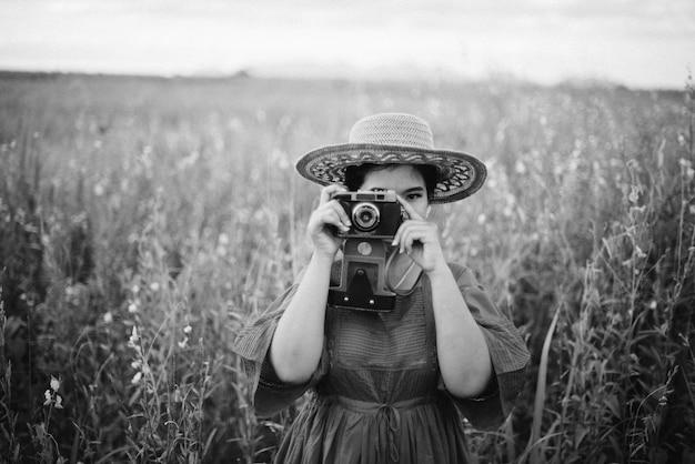 Femme prenant une photo avec un vieil appareil photo en noir et blanc