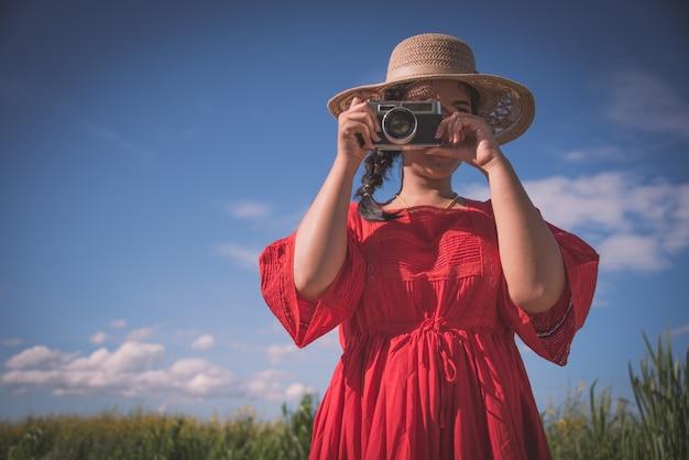 Femme prenant une photo avec un vieil appareil photo
