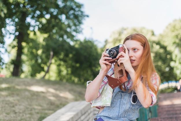 Femme prenant la photo avec le vieil appareil photo