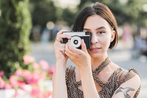 Femme prenant des photos dans le parc avec caméra