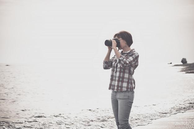 Femme prenant des photos avec dslr sur la plage