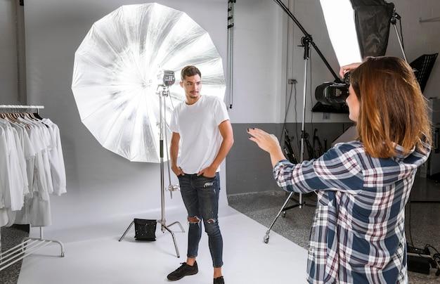 Femme prenant des photos du modèle posant