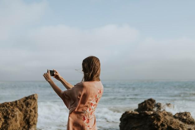 Femme prenant des photos avec son téléphone sur la plage