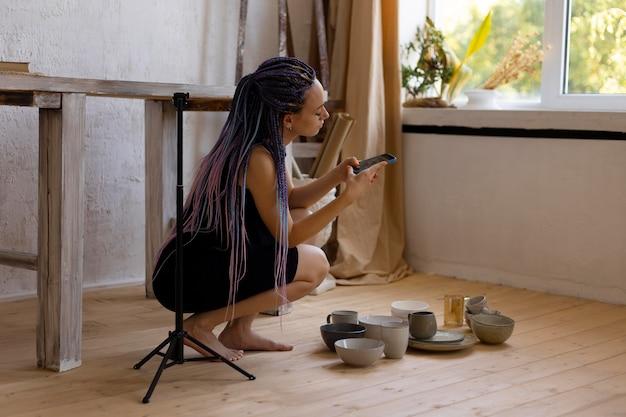 Femme prenant des photos d'ustensiles de cuisine en céramique à la maison