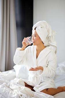 Femme prenant des pilules et un verre d'eau pour le traitement, le matin. belle femme boit des vitamines pour la prévention des maladies. concept de bien-être et de santé