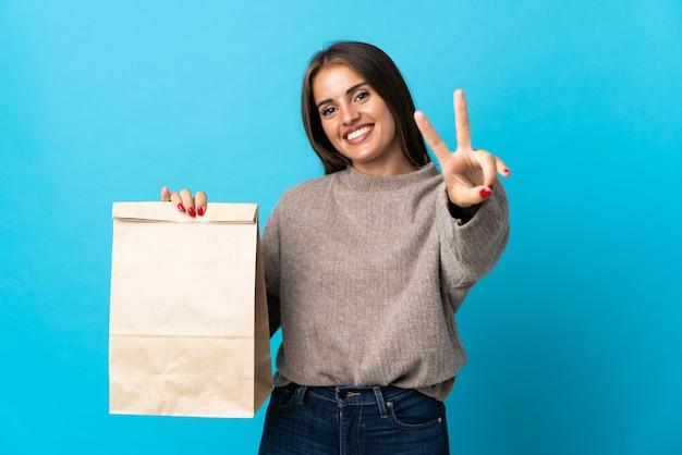 Femme prenant un sac de plats à emporter isolé sur bleu souriant et montrant le signe de la victoire