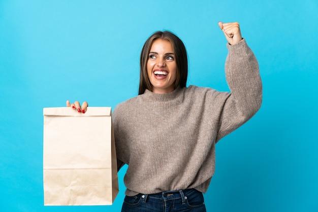 Femme prenant un sac de plats à emporter isolé sur mur bleu célébrant une victoire