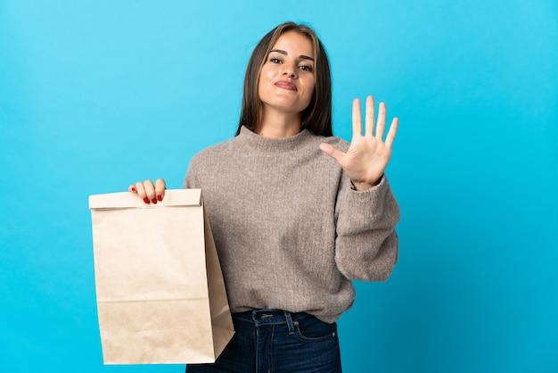 Femme prenant un sac de plats à emporter isolé sur mur bleu en comptant cinq avec les doigts