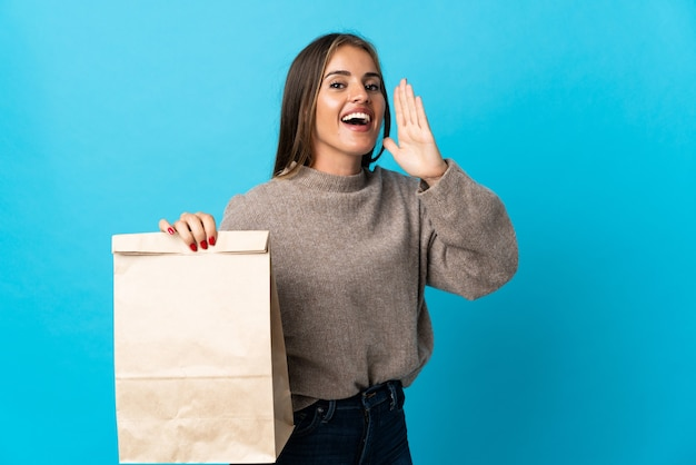 Femme prenant un sac de plats à emporter isolé sur mur bleu en criant avec la bouche grande ouverte
