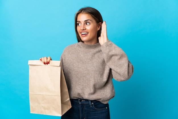 Femme prenant un sac de plats à emporter isolé sur mur bleu en écoutant quelque chose en mettant la main sur l'oreille