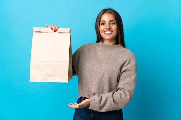 Femme prenant un sac de plats à emporter isolé sur mur bleu étendant les mains sur le côté pour inviter à venir