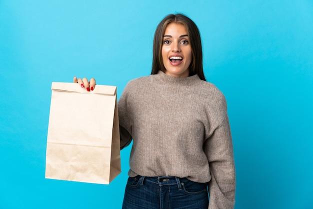Femme prenant un sac de plats à emporter isolé sur un mur bleu avec une expression faciale surprise