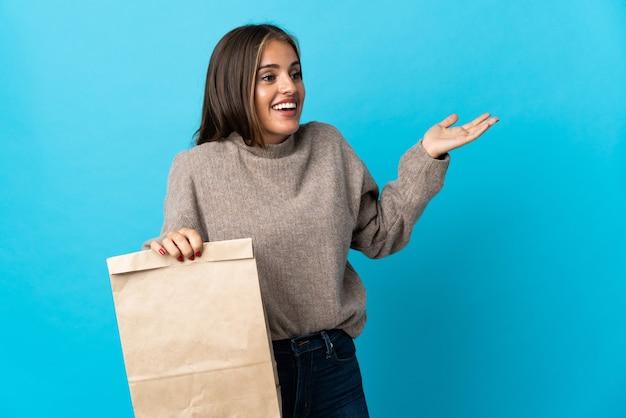 Femme prenant un sac de plats à emporter isolé sur un mur bleu avec une expression de surprise tout en regardant côté
