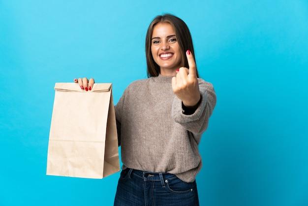 Femme prenant un sac de plats à emporter isolé sur mur bleu faisant le geste à venir
