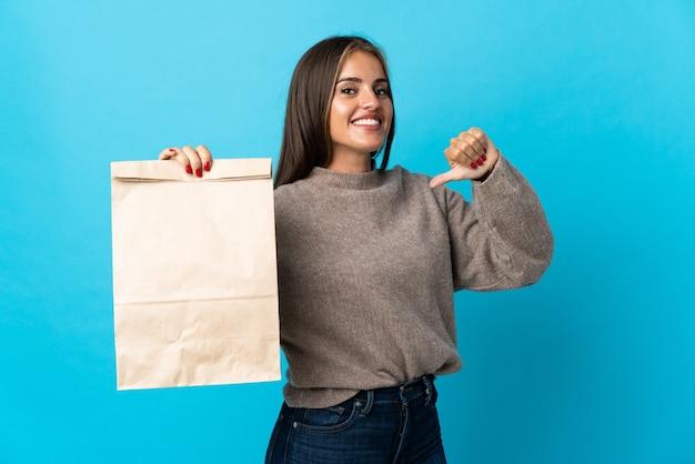 Femme prenant un sac de plats à emporter isolé sur un mur bleu fier et satisfait de soi