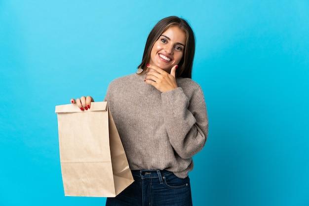 Femme prenant un sac de plats à emporter isolé sur mur bleu heureux et souriant