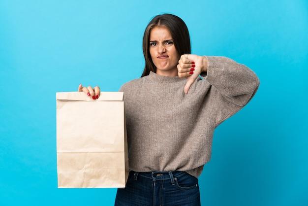 Femme prenant un sac de plats à emporter isolé sur un mur bleu montrant le pouce vers le bas avec une expression négative