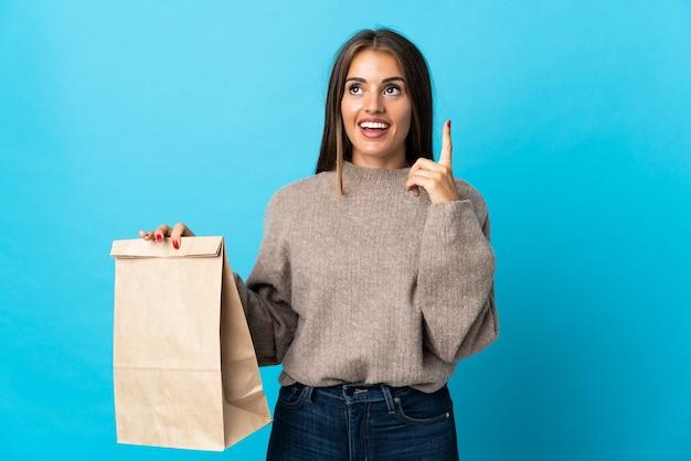Femme prenant un sac de plats à emporter isolé sur mur bleu pensant une idée pointant le doigt vers le haut