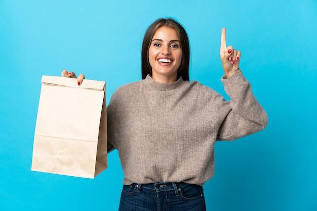 Femme prenant un sac de plats à emporter isolé sur un mur bleu pointant vers le haut une bonne idée