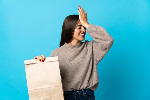 Femme prenant un sac de plats à emporter isolé sur mur bleu a réalisé quelque chose et l'intention de la solution