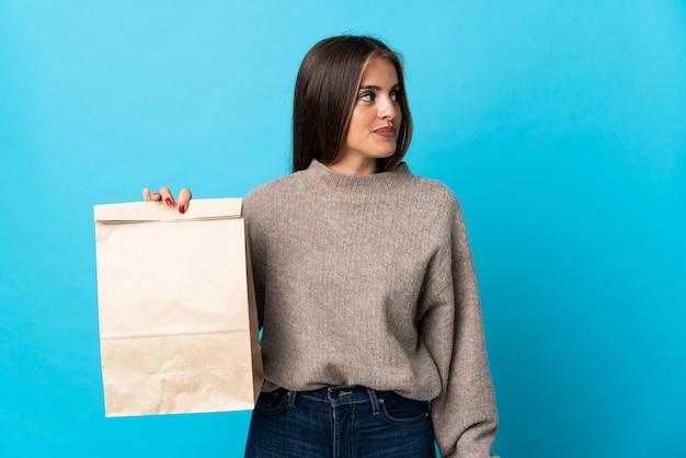 Femme prenant un sac de plats à emporter isolé sur mur bleu à la recherche sur le côté