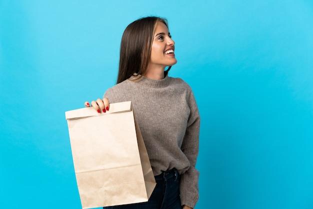 Femme prenant un sac de plats à emporter isolé sur mur bleu en riant en position latérale