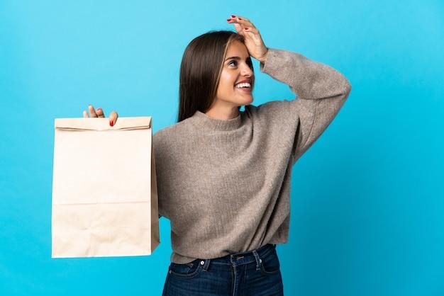 Femme prenant un sac de plats à emporter isolé sur mur bleu souriant beaucoup