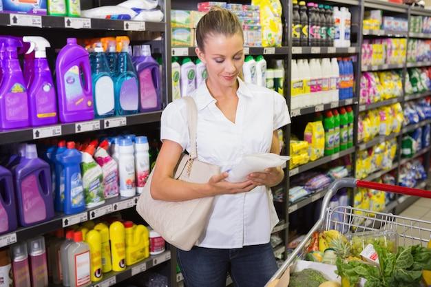 Femme prenant un sac de riz dans l'étagère de l'allée au supermarché