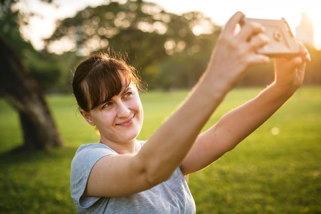 Femme prenant un selfie au parc