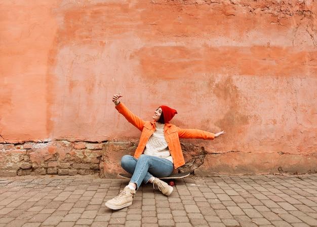Femme prenant un selfie à l'extérieur avec espace copie