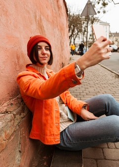 Femme prenant un selfie à l'extérieur
