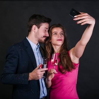 Femme prenant selfie avec homme en fête