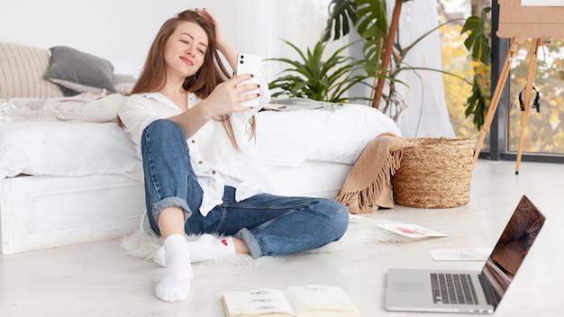 Femme prenant un selfie à la maison