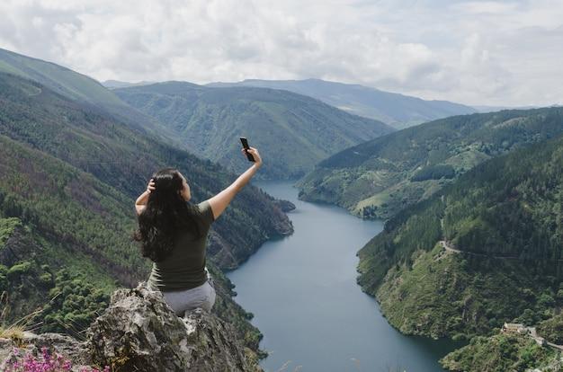 Femme prenant selfie avec la rivière