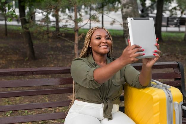 Femme prenant un selfie avec sa tablette à l'extérieur