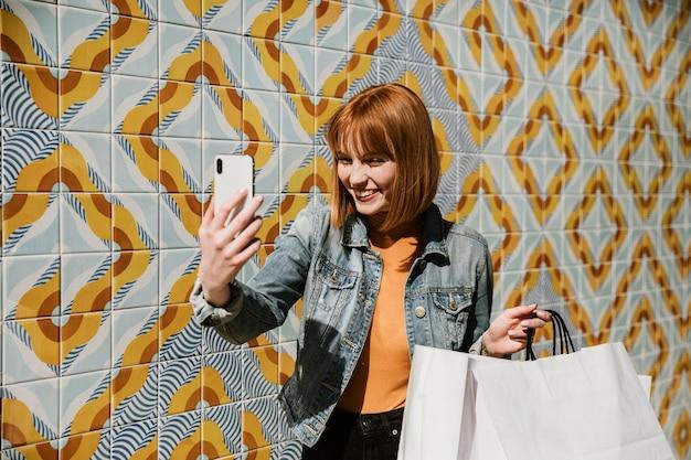 Femme prenant un selfie avec ses sacs à provisions